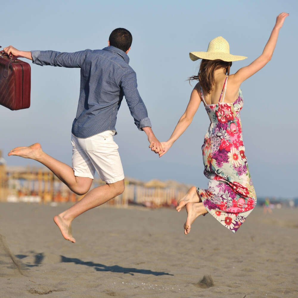 Man and Woman at the Beach Jumping in the Sand